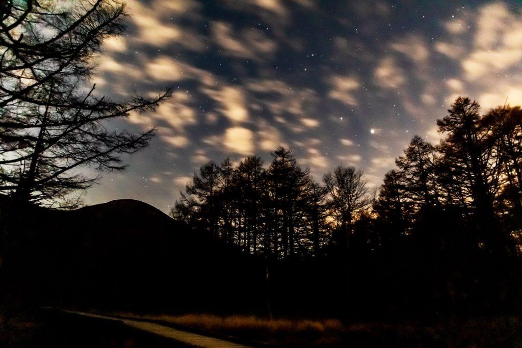 2020年11月1日、信州たてしな 白樺高原の御泉水自然園から、夜の星空風景。池にかかる木の橋と蓼科山と星空。