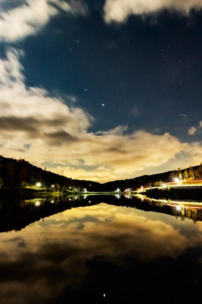 2020年10月27日、信州たてしな 白樺高原の白樺湖畔から南西方向、夜の星空風景。鏡のような白樺湖の湖面と請雨空に拡がる星空。