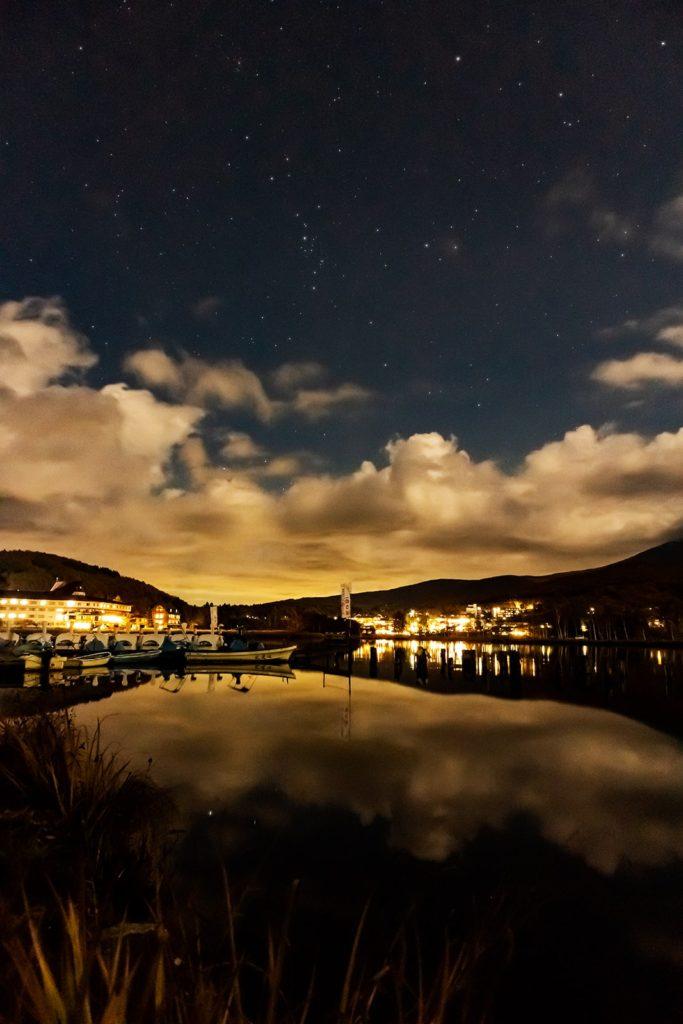 2020年10月27日、信州たてしな 白樺高原の白樺湖畔から北東方向、夜の星空風景。鏡のような湖面に写る星と上空に輝く星々。アンドロメダ銀河もハッキリと写っている。