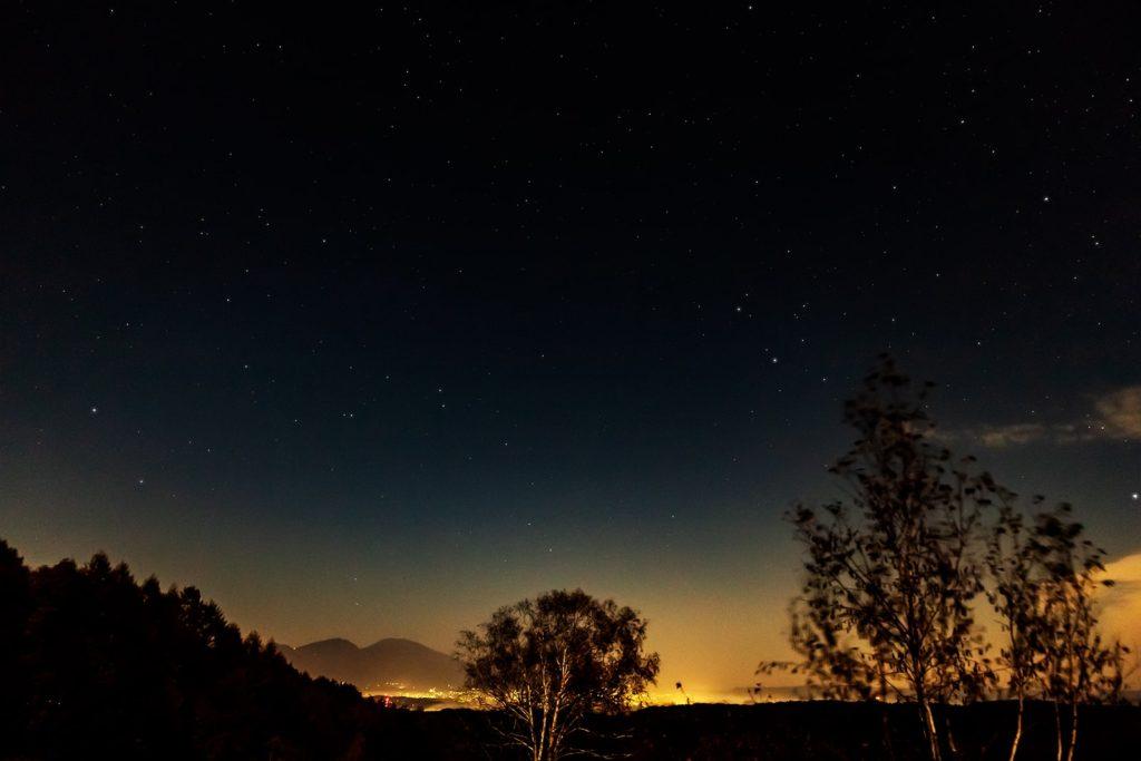 2020年10月28日、信州たてしな 白樺高原の蓼科第二牧場から北東方向、夜の星空風景。佐久平の夜景の向こうに浮かぶ浅間山と上空に拡がる満天の星星。