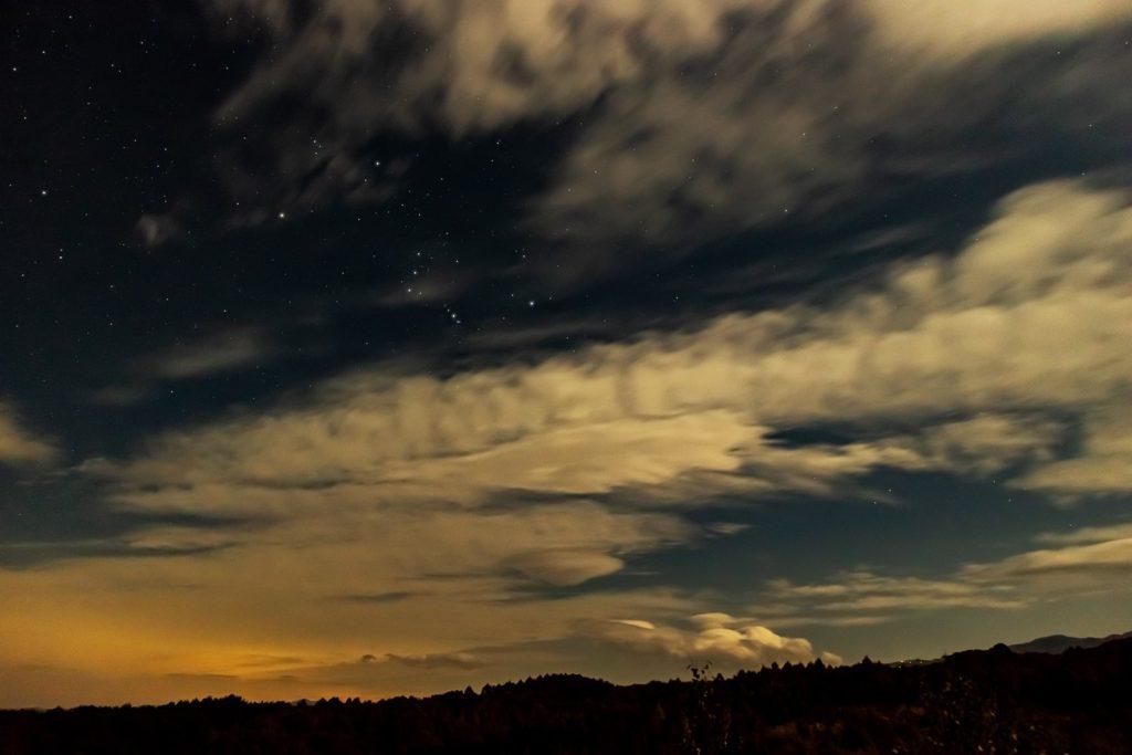 2020年10月28日、信州たてしな 白樺高原の蓼科第二牧場から東方向、夜の星空風景。雲の影から出ている冬の星座オリオン座。