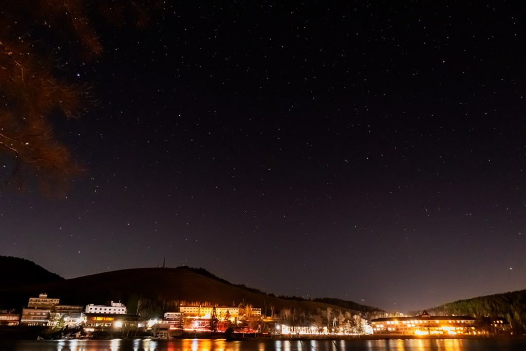 2020年11月20日、信州たてしな 白樺高原の白樺湖畔から北方向、夜の星空風景。北の方角、白樺湖越しに見える星空にはりゅう座や北極星、こぐま座などが見える。