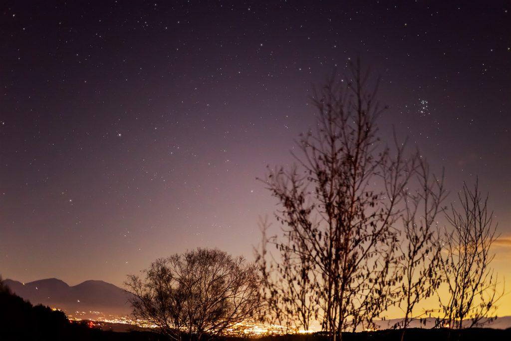 2020年11月23日、信州たてしな 白樺高原の三望台から北東方向、夜の星空風景。佐久平の夜景と浅間のシルエット、空にはプレアデス星団(すばる)やぎょしゃ座が輝く