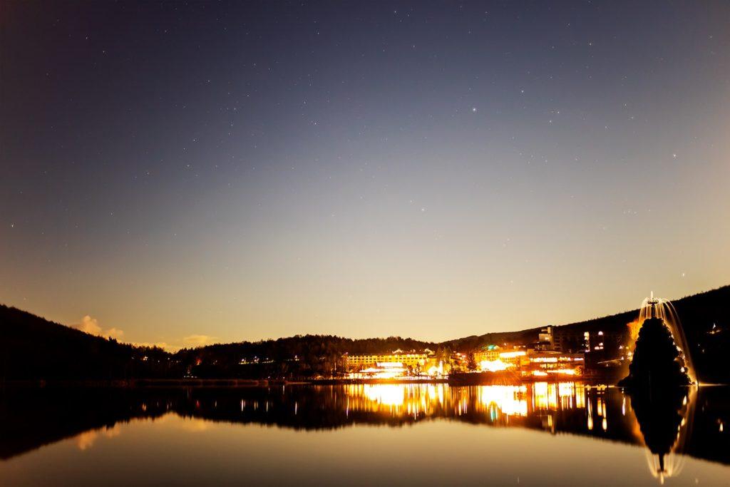 2020年11月30日、信州たてしな 白樺高原の白樺湖畔から北東方向、夜の星空風景。鏡のような湖面に写る景色と上空のぎょしゃ座。