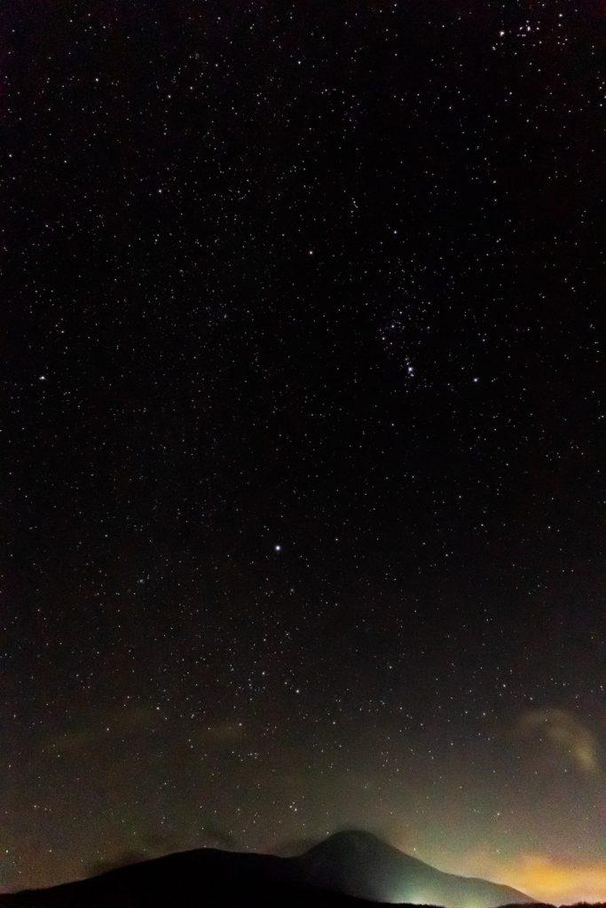 2020年12月12日、信州たてしな 白樺高原の蓼科第二牧場から南方向、夜の星空風景。うっすらと雲がかかった蓼科山と星空。冬の星座オリオン座や冬の大三角形(シリウス、ベテルギウス、プロキオン)が見える。