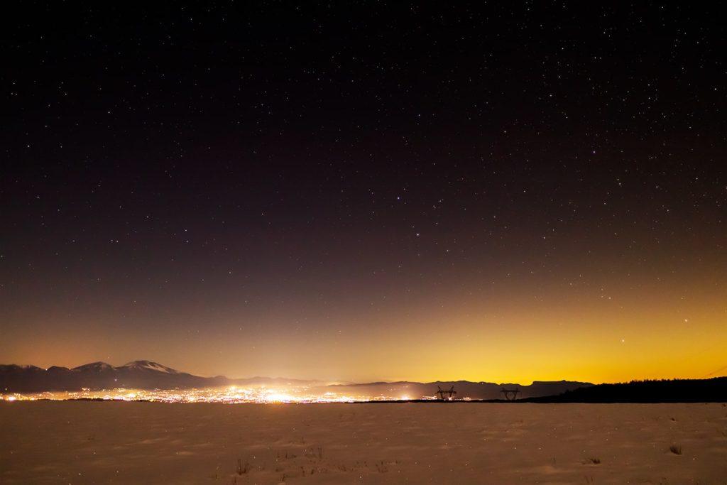 2020年12月21日、信州たてしな 白樺高原の蓼科第二牧場から北東方向、夜景と星空の風景。スキリと晴れた夜空に広がる満天の星と佐久平の夜景。牧場の白い雪と相まって絶景を創り出していた。