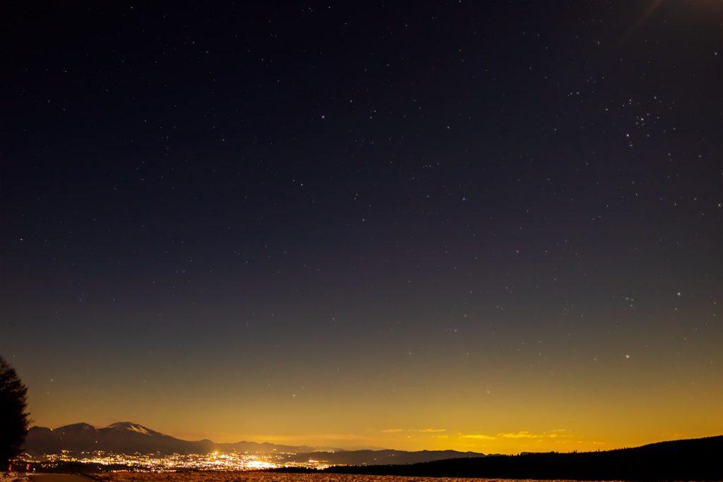 2020年12月26日、信州たてしな 白樺高原の蓼科第二牧場から北東方向、夜景と星空の風景。佐久平の夜景と浅間山の上空に輝くぎょしゃ座など。
