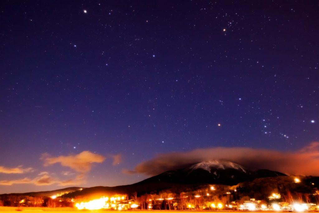 2021年1月6日、信州たてしな 白樺高原の白樺湖畔から、夜の星空風景。蓼科山には山頂付近に雲がかかるが上空のオリオン座やぎょしゃ座もきれいに見えている。