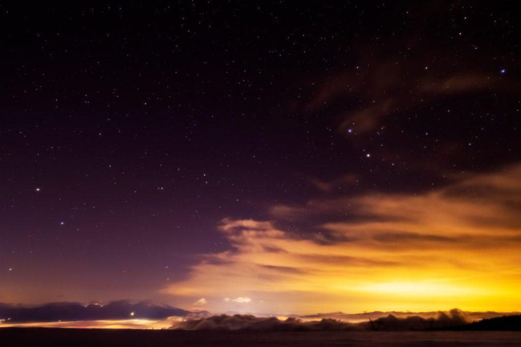 2021年1月12日、信州たてしな 白樺高原の蓼科第二牧場から、夜の雲海と星空の風景。雲海にうかぶ浅間山と上空に輝くふたご座。