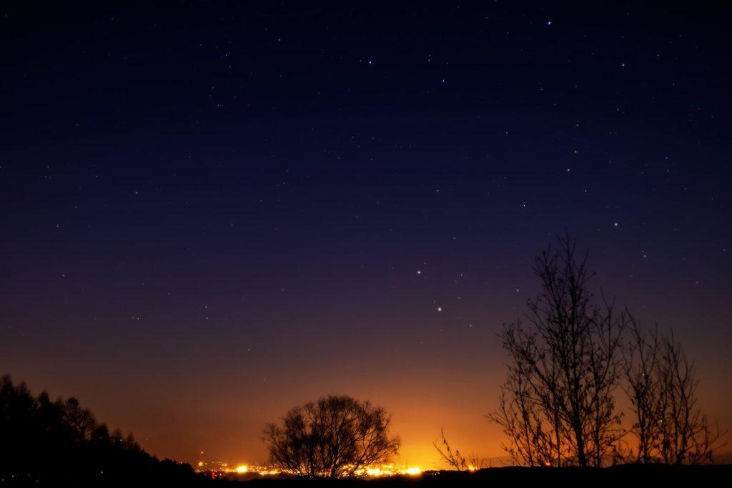 2021年1月14日、信州たてしな 白樺高原の三望台から北東方向、夜景と星空の風景。雲の少ない北東方向に見える夜景と上空に輝くふたご座