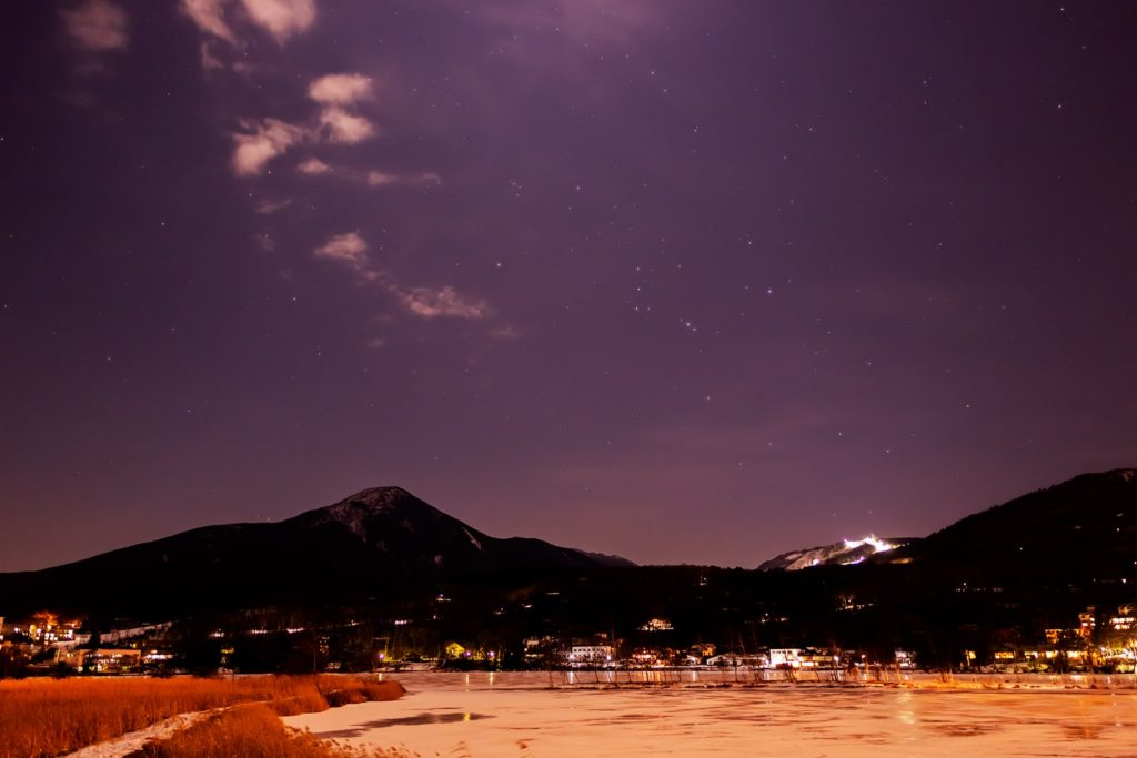 2020年12月27日、信州たてしな 白樺高原の白樺湖畔から、夜の星空風景。白樺湖越しに見る蓼科山とオリオン座。