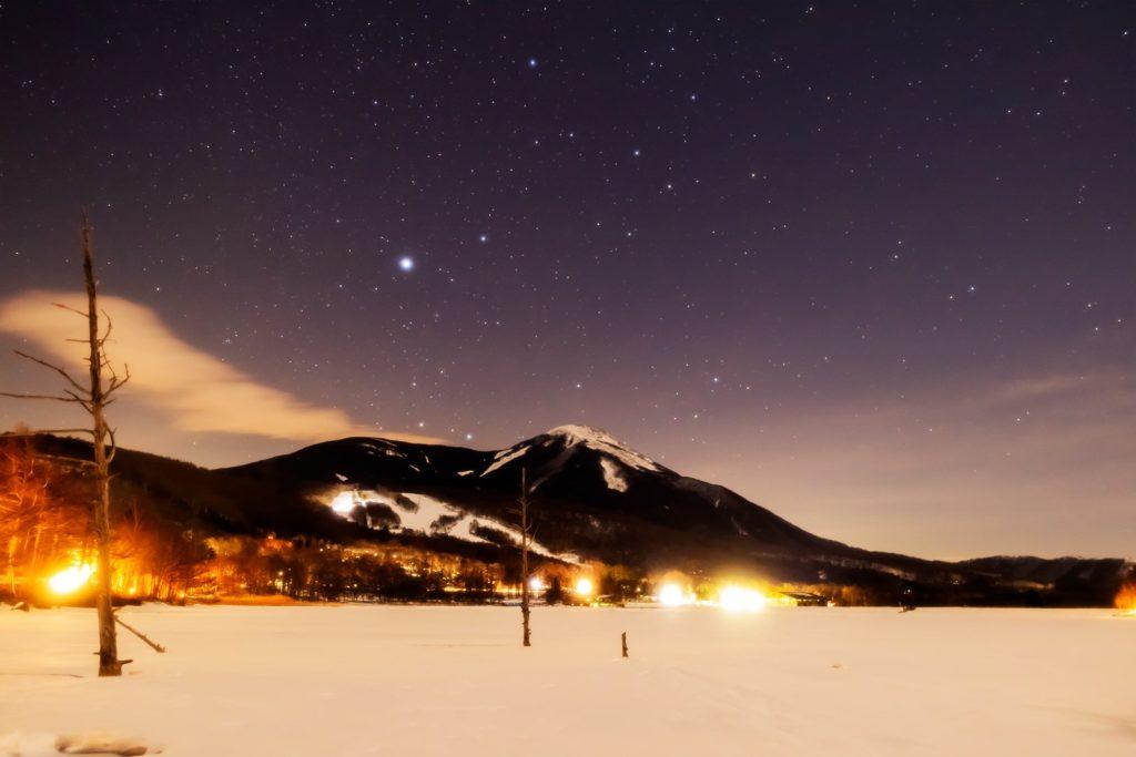 2021年1月21日、信州たてしな 白樺高原の女神湖から、蓼科山と夜の星空風景。すっかりと凍結した女神湖から見えるおおいぬ座のシリウス